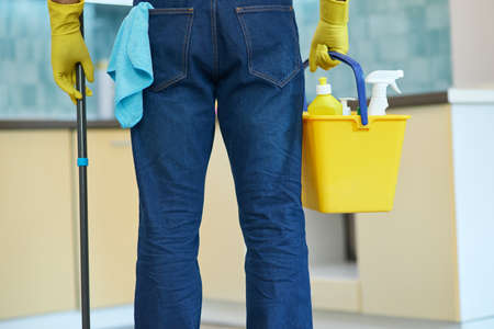 Professional house cleaning. Cropped shot of professional male cleaner holding plastic bucket with detergents and mop while getting ready for cleaning floor in the kitchen 免版税图像