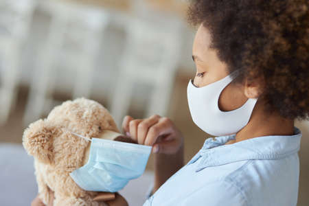 Mixed race teen girl child in protective face mask holding a teddy bear wearing a mask