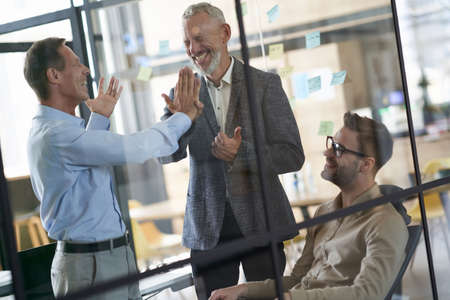 Two excited mature businessmen giving high five to each other while having a meeting with colleagues in the modern office