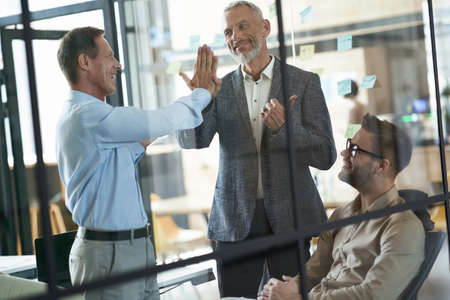 Good job. Two happy mature businessmen giving high five to each other while having a meeting with colleagues in the modern office
