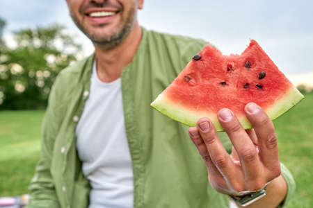Cropped shot of happy young man smiling at camera while holding watermelon slice, sitting in the green park on a summer day 免版税图像