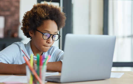 Enthusiastic mixed race teen schoolgirl listening to her teacher while using laptop during online video lesson, studying from home Фото со стока