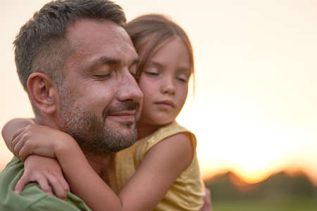 Close up shot of young father and adorable little daughter embracing each other, posing with eyes closed while spending time outdoors in the park on a summer day