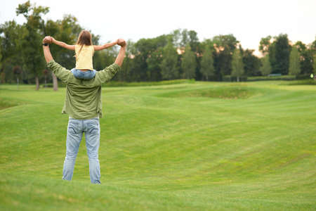 Rear view of little girl sitting on fathers shoulders and holding each other hands, standing in a green field on a warm day, spending time together outdoors