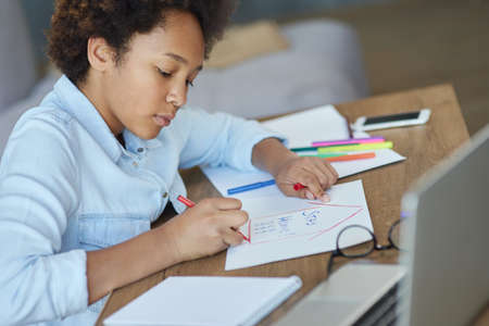 Portrait of focused teen schoolgirl using markers while doing her homework with laptop computer at home 免版税图像