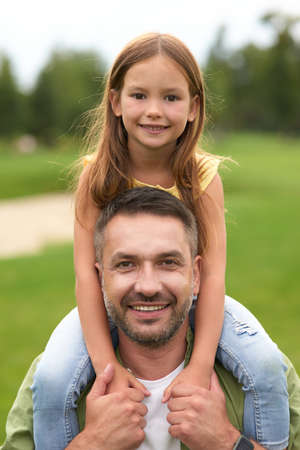 Portrait of happy dad holding his cute little daughter on shoulders and smiling at camera while having fun together in the green park on a warm day