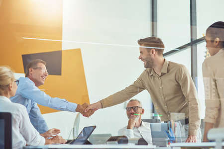 Two excited businessmen shaking hands and smiling while having a meeting with colleagues in the modern office
