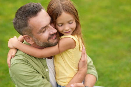 Portrait of happy young father and adorable little daughter hugging each other, standing with eyes closed while spending time in the green park on a summer day 免版税图像