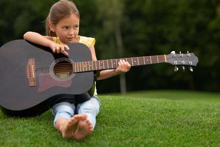 Adorable little girl looking aside and holding guitar sitting on a green grass in park, spending time with parents outdoors