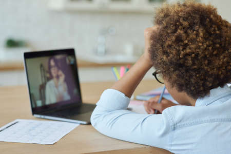 Rear view of mixed race teen schoolgirl drawing on paper with marker, using laptop while having online video lesson with teacher, sitting at home