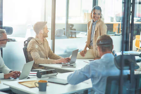 Young cheerful mixed race female office worker discussing something with colleagues while sitting in board room in the modern office, business people having a meeting 免版税图像