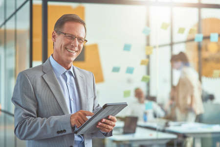 Cheerful mature businessman in classic wear holding digital tablet and smiling at camera while standing in the modern office