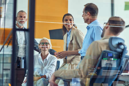 Successful team at work. Group of multi ethnic business people discussing something, communicating and smiling while having a meeting in modern office 免版税图像