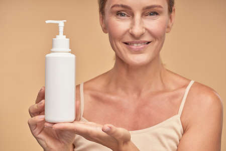 Attractive mature female holding jar of cream 免版税图像