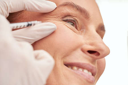 Beauty procedure. Close up of a beautiful mature woman receiving hyaluronic acid injection by beautician