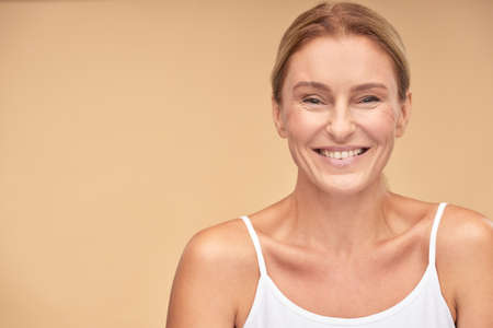 Portrait of happy beautiful mature woman smiling at camera isolated over beige background 免版税图像