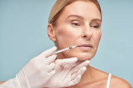 Attractive mature caucasian woman making lip augmentation procedure by cosmetologist while standing against blue background