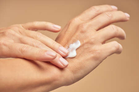 Female hands with nude manicure on nails applying hand cream
