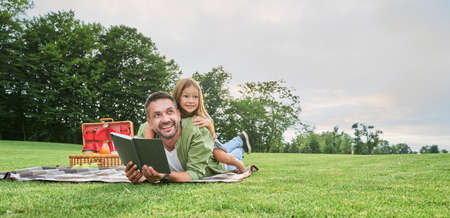Cheerful cute little girl spending time with her father, reading a book while having picnic in the park 免版税图像