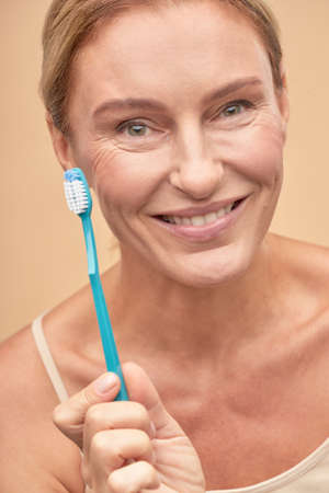 Happy pretty woman going to brush her teeth