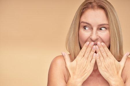 Surprised woman posing in studio on beige background 免版税图像