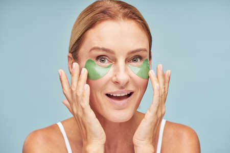 Smiling mature female with under eye moisturizing patches in studio