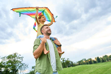 Happy father carrying cute little daughter on his shoulders while she is holding colorful kite 免版税图像