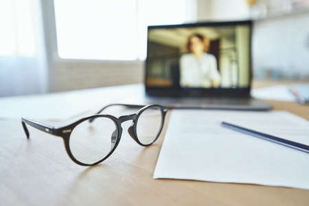 Close up of eyeglasses on the table. Laptop screen with female teacher communicating via video chat app in the background