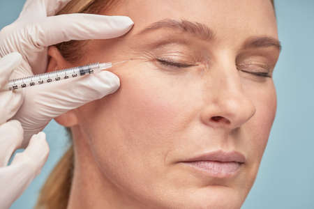Close up portrait of a beautiful mature woman keeping eyes closed while receiving hyaluronic acid injection by beautician