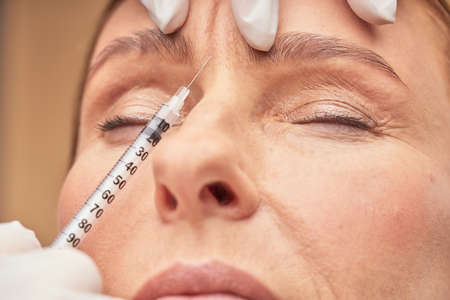 Anti Aging procedures. Close up shot of beautician in protective gloves making cosmetic injection in female forehead