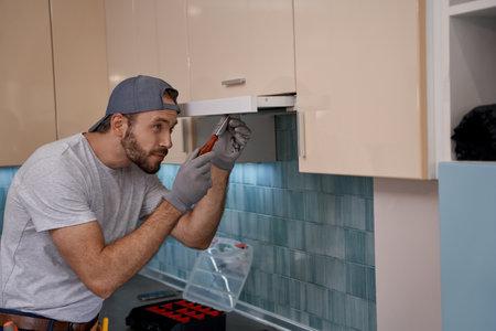 Young caucasian repairman installing kitchen hood using screwdriver