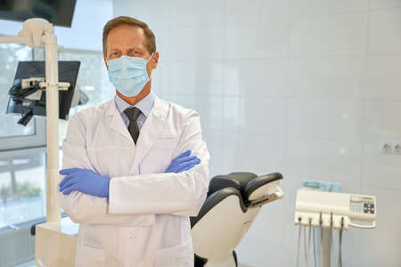 Male dentist in his uniform posing at the clinic