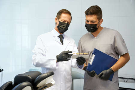 Two dental specialists discussing teeth-whitening at clinic