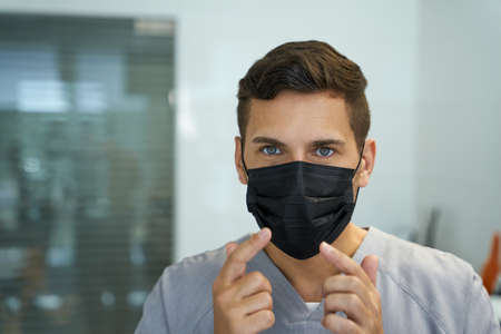 Mindful doctor showing a correct way to wear a mask 免版税图像