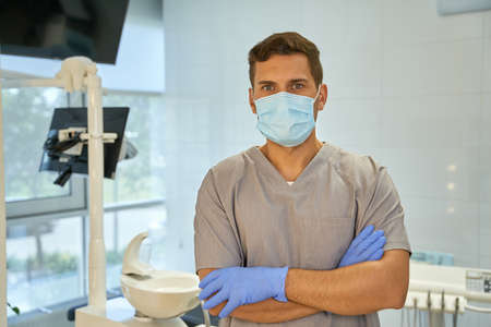 Male dental technician wearing mask and gloves at workplace