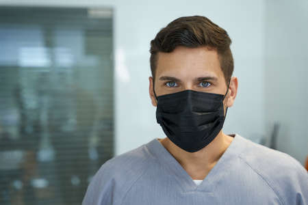 Young male doctor wearing mask and posing for camera