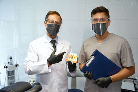 Dentists in personal protective equipment posing at workplace 免版税图像