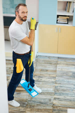 Making your house clean. Full length shot of a man, professional male cleaner wearing gloves looking at camera, holding mop while cleaning floor in the kitchen Фото со стока