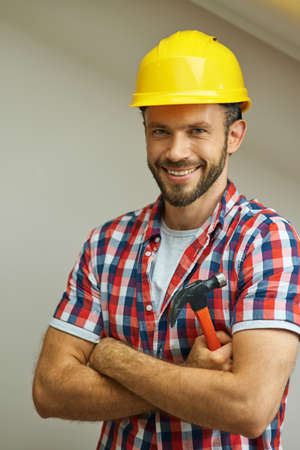 Portrait of joyful handyman wearing a helmet smiling at camera, standing with arms crossed and holding a hammer while posing indoors