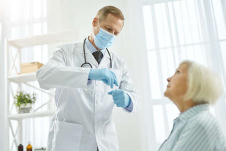 Doctor in medical mask testing old woman for infection