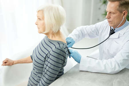 Serious doctor examining old woman with stethoscope in clinic