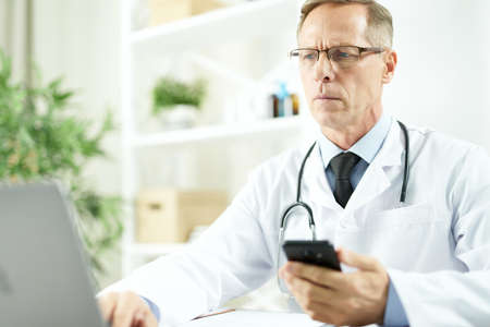 Serious doctor holding cellphone and using laptop at work Stock Photo