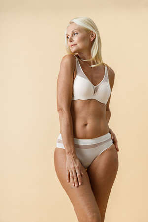 Mature blonde woman with fit body in white underwear looking aside while posing isolated over beige background
