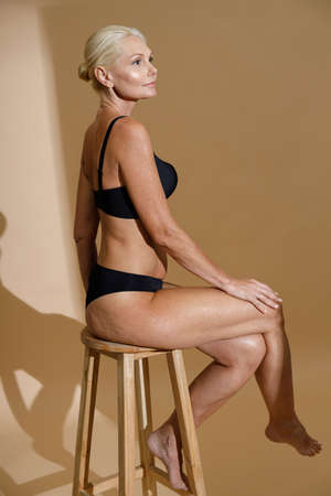 Side view of beautiful mature woman in black underwear looking aside, sitting on a chair while posing half in studio isolated over beige background