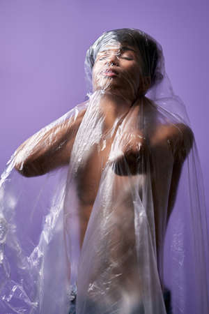 Portrait of young man standing in plastic bag on muscular body. Claustrophobia problem