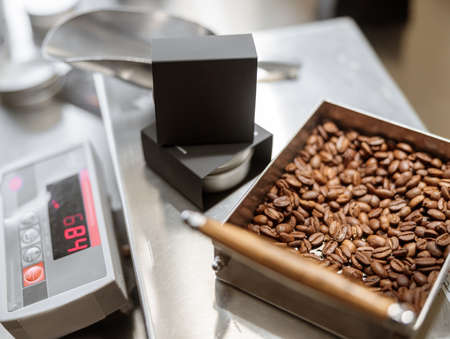 Electronic scales with black box and roasted coffee beans Banque d'images
