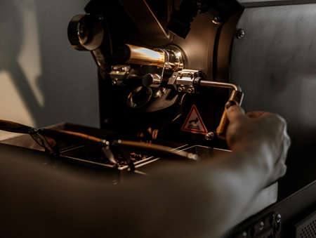Male worker using industrial coffee roasting machine at factory Banque d'images