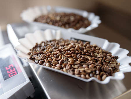 Bowls of roasted coffee beans on electronic scales