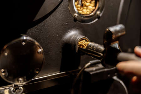 Male worker using industrial coffee roasting machine