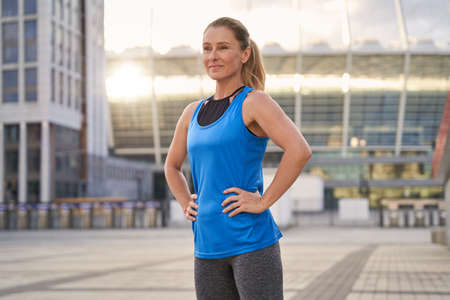 Portrait of beautiful middle aged woman in sportswear smiling away, standing outdoors ready for running in the city Banque d'images